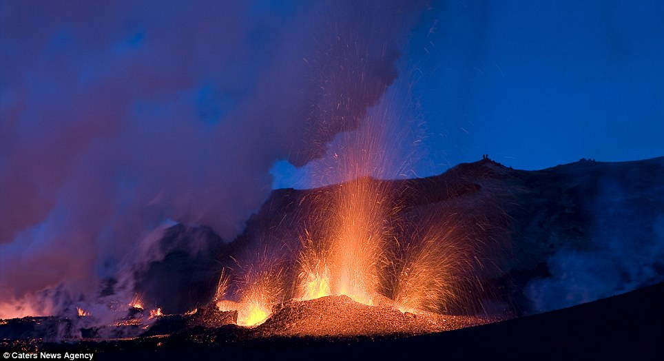 Spitting: A fierce volcano blows orange lava, creating a wonderful contrast with the sky