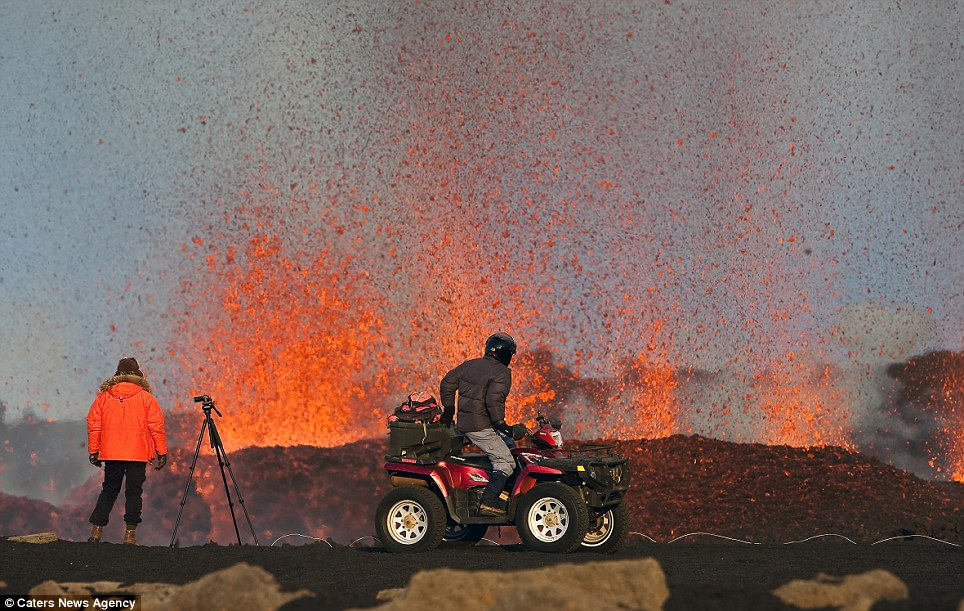 Danger: A couple of photographers look ready to move if the lava gets too close to them as it spits orange lava
