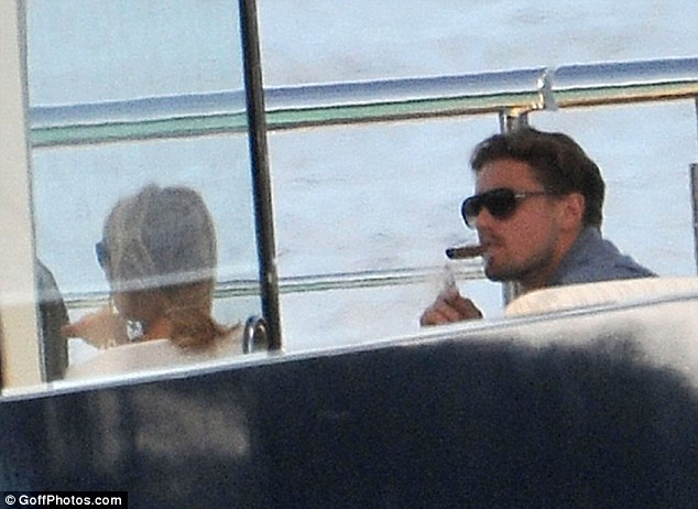 Up in smoke: Leo takes a drag on a cigar as he relaxes on board