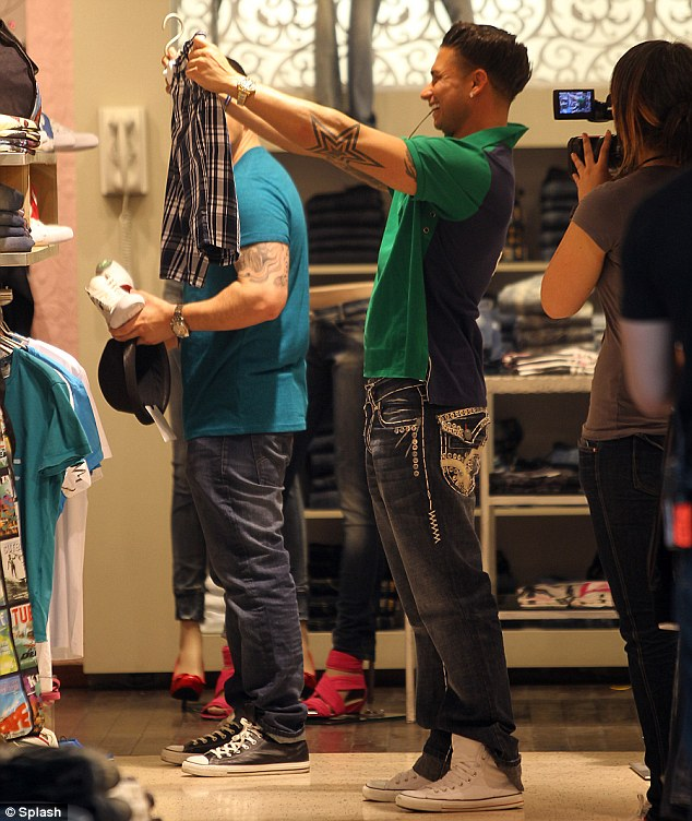 Nice threads: Pauly D examines a pair of short inside a store as Vinny checks out a hat