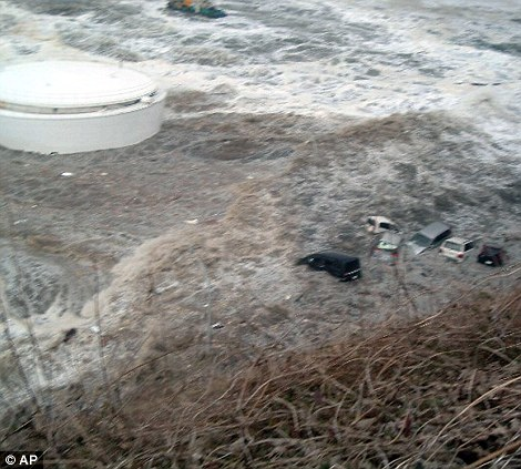 Devastation: Cars are swept away by waves of tsunami near tanks of heavy oil for the Unit 5 of the Fukushima Dai-ichi nuclear plant