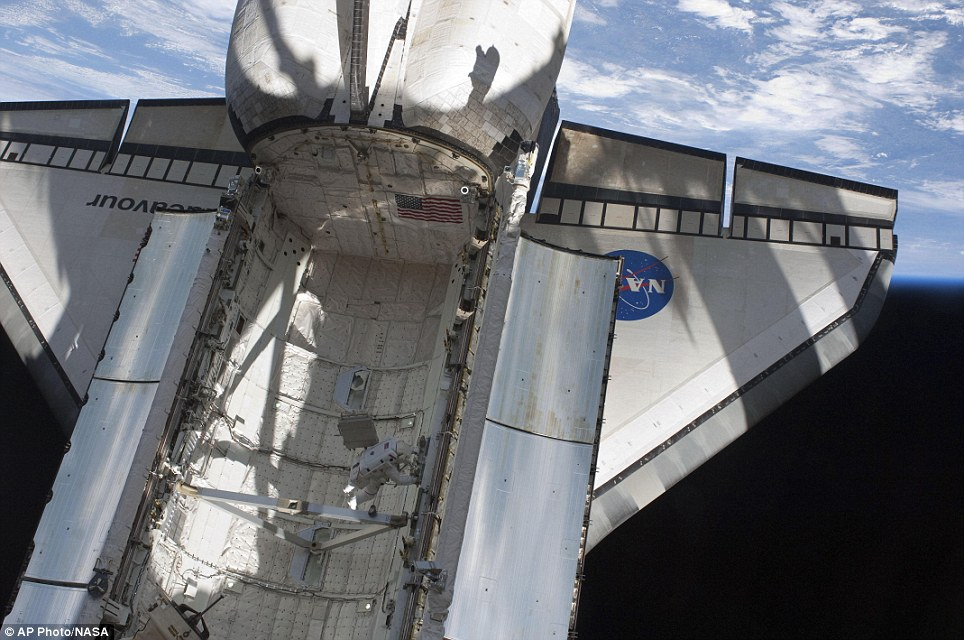 Room with a view: Astronaut Andrew Feustel works in the space shuttle Endeavour's payload bay during the mission's first spacewalk at the International Space Station yesterday
