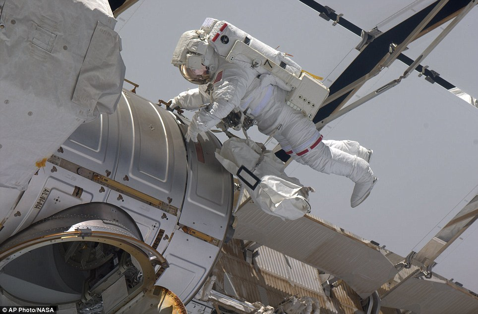 High-flyer: Astronaut Gregory Chamitoff makes his way back to the hatch at the end of his first spacewalk yesterday