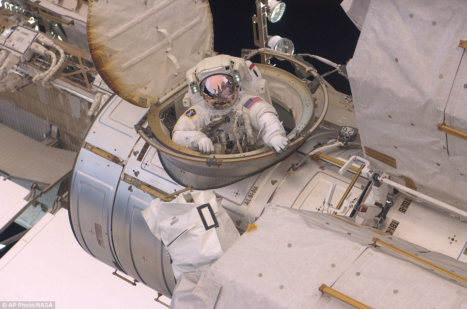 Job done: Andrew Feustel enters the hatch on the International Space Station having carried out repairs