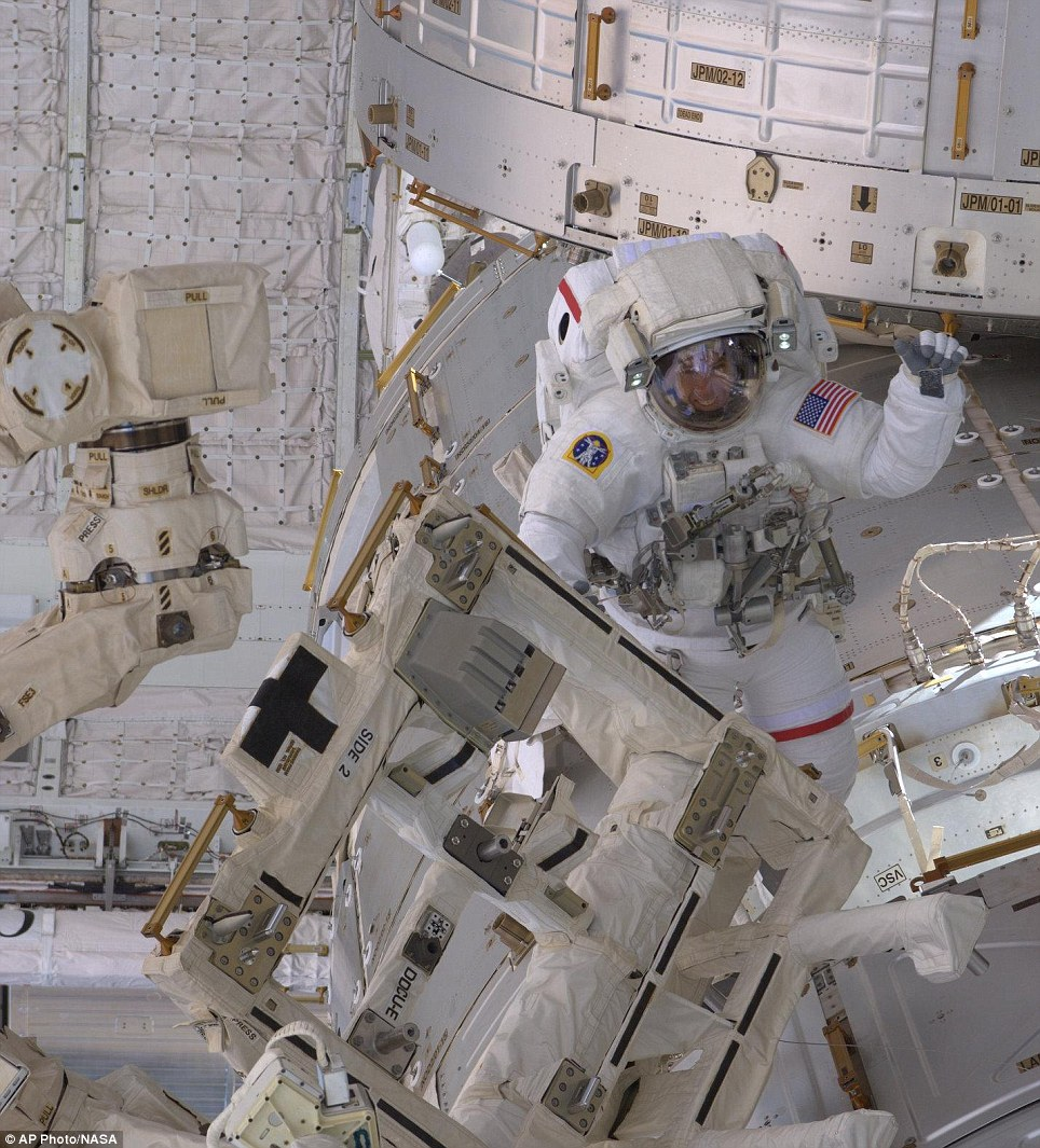 Vital work: Andrew Feustel works in the vacuum of space installing an antenna and connecting power cables