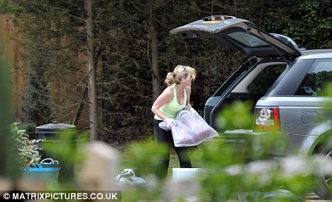 Cleaning up: Anthea keeps things tidy and loads the car outside her home in Surrey