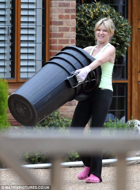 Grimace: Anthea struggles with four large bins during a tidy up. She later turned her attention to vacuuming and loading up a van