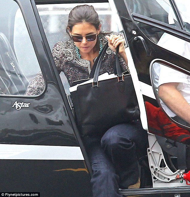 Arriving in style: Katie steps out of a helicopter having flown out from Miami earlier in the day