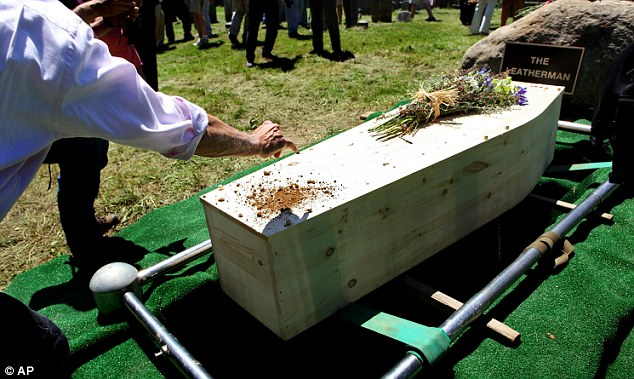 Final farewel: Tony Godino of Bedford, N.Y. pays his respects with soil at the end of a reburial ceremony