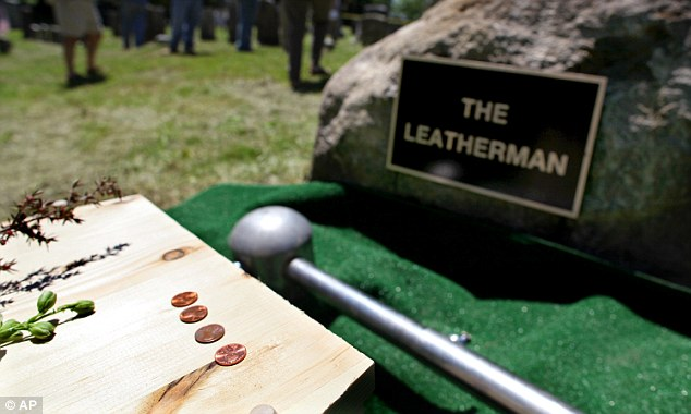 """Tribute to the unknown: Pennies, placed by Dan DeLuca who wrote """"The Old Leather Man: Historical Accounts of a Connecticut and New York Legend,"""" lay on a pine casket that contains soil from the former grave the Leatherman at Wednesday's reburial ceremony"""
