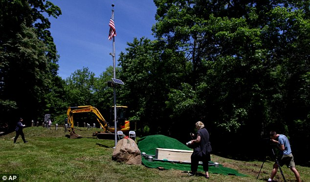 Oddity: Photographers and sightseers walk near the reburial site before the ceremony began in Ossining, NY