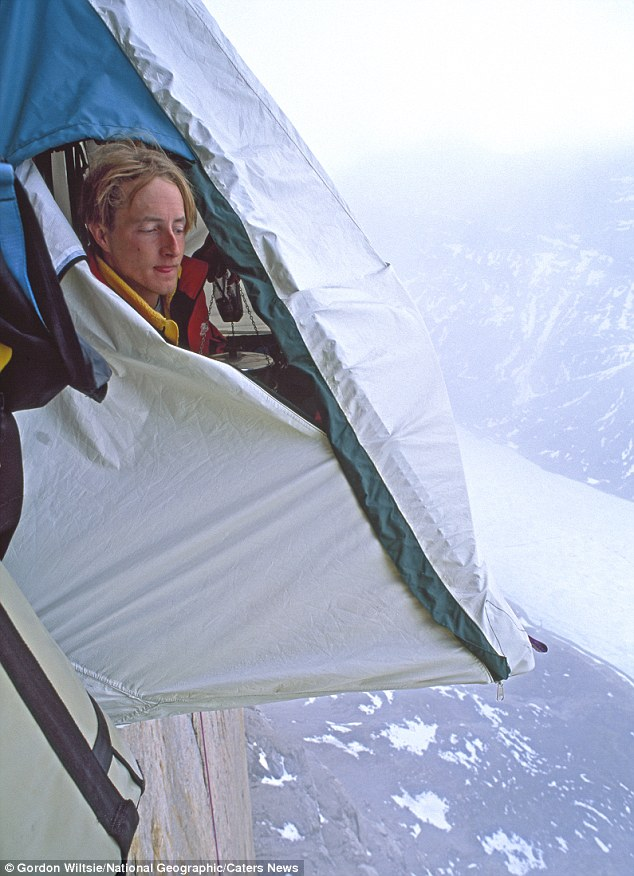 Don't look down: A climber peaks out of his tent high up on Great Sail Peak, on Canada's Baffin Island