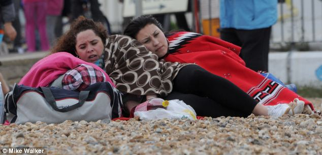 Cold: Two day trippers huddle together for warmth on the beach at Southsea, Hants, yesterday, but experts predict hot weather will return for the weekend