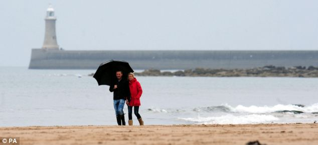 Two walkers brave the wet weather on an almost empty beach in Tynemouth, North Tyneside