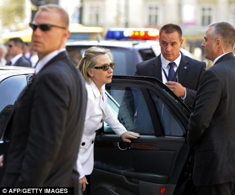 Protected: Secretary of State Hillary Clinton steps out of her limousine, surrounded by security men