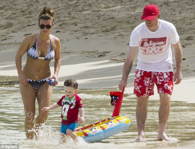 Family time: Coleen and Wayne play in the surf with their 18-month-old son Kai