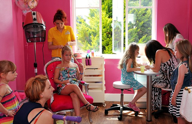 Pampered: A little girl waits patiently as she has her hair done in the salon which caters for children up to 13, in Braintree, Essex