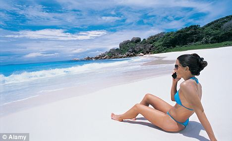 Woman Sunbathing on a Tropical Beach Using Her Mobile Phone.