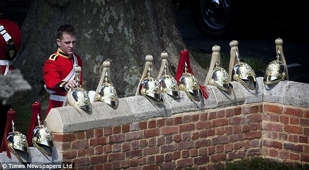 Hat's that: A member of the Household Cavalry places his helmet alongside others on a wall near the chapel