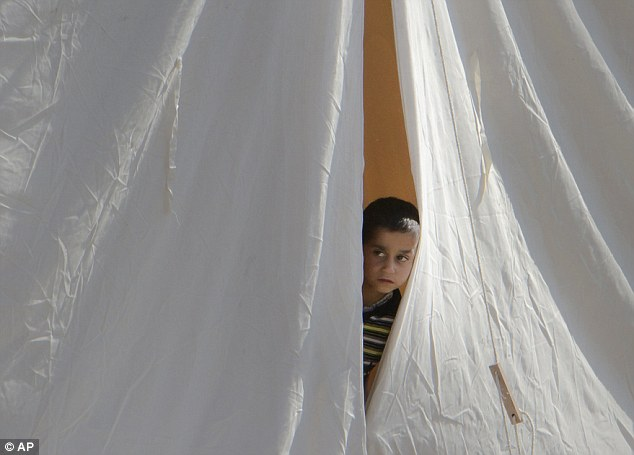 A young boy peeps out of his makeshift home in the refugee camp on the Turkey/Syria border