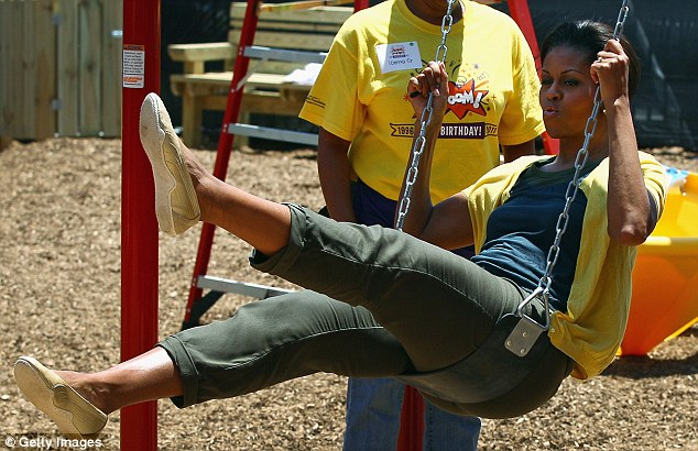 Swinging by: Wearing khaki trousers, a navy T-shirt and yellow cardigan, Michelle plays on a swing she has just helped build at the playground