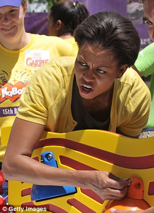 Michelle Obama has to do some hard labor while helping to build a Kaboom playground in Washington DC at Southeast Public Charter School.