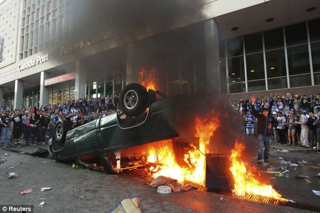 Riots: Cars were overturned and set on fire in downtown Vancouver after the Canucks lost 4-0