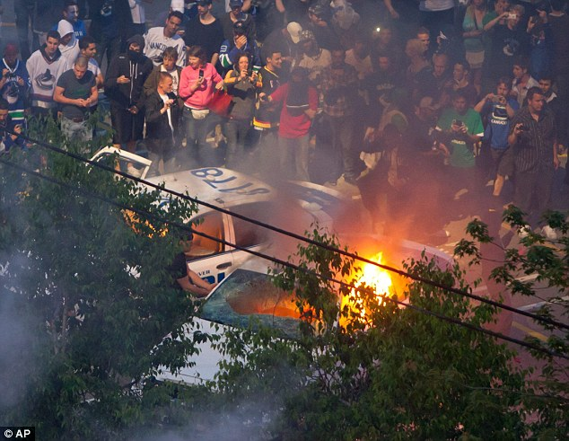 People gathered to take photographs of a burning car next to a damaged police car
