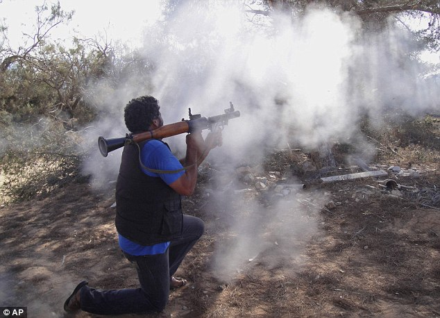 On the attack: A rebel fighter fires towards pro-Gadaffi forces at the front line of Dafniya, west of Misrata. Despite Nato airstrikes, the rebels are struggling to make advances on the ground