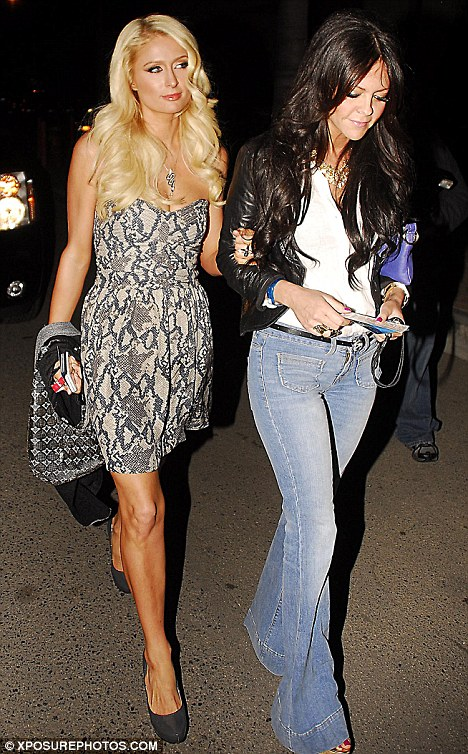 Glamorous: Paris Hilton makes her way into the U2 concert with a friend