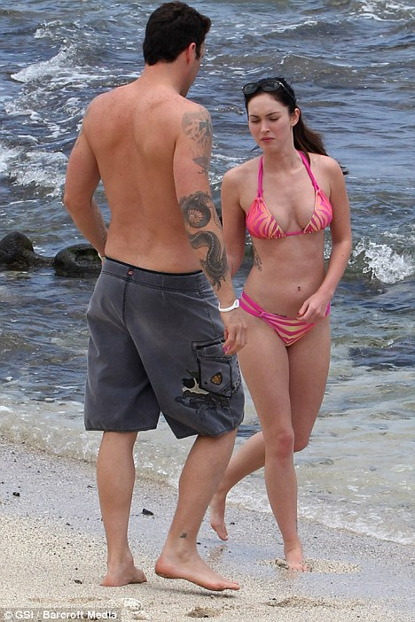 Fun in the sun: Both Megan and her husband have several tattoos on their bodies, here we see Brian's arm inking