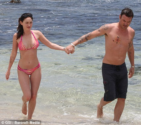 Paradise: The couple take a stroll through the water during their Hawaiian holiday