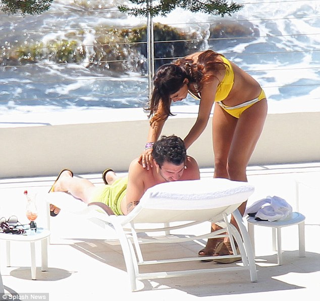 Chilling out: Cesc gets a massage from the mystery woman
