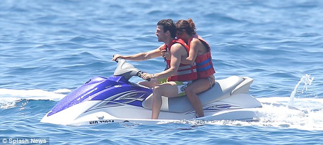 Hold on tight: The couple's day gets a little more exciting with a daring ride through the waves