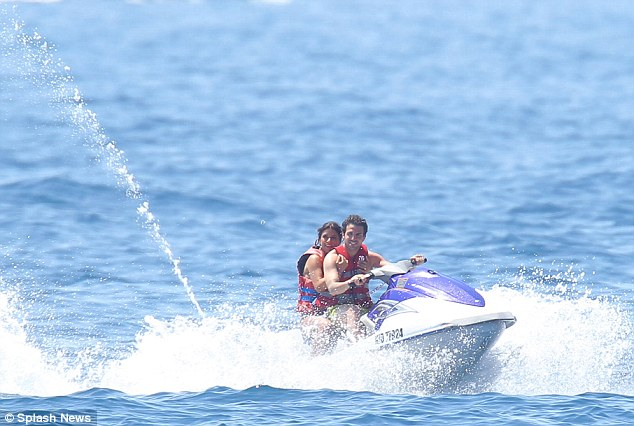 Time for action: The midfielder speeds through the water with his companion keeping a firm grip on her boyfriend
