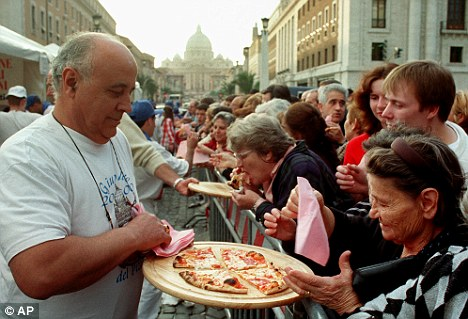Pizzaioli: Romans, pilgrims and the faithful eat free pieces of pizza in Rome's Via della Conciliazione, overlooked by St Peter's Basilica, as part of the Jubilee of the Pizza Makers