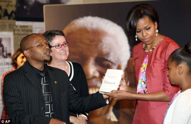 Present: Sello Hatang and Sahm Venter from the Nelson Mandela Foundation present Mrs Obama and Sasha with Nelson Mandela's newest book 'Nelson Mandela by Himself'