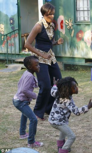 Feel the beat: Michelle Obama dances with children as she visits a community centre in Johannesburg