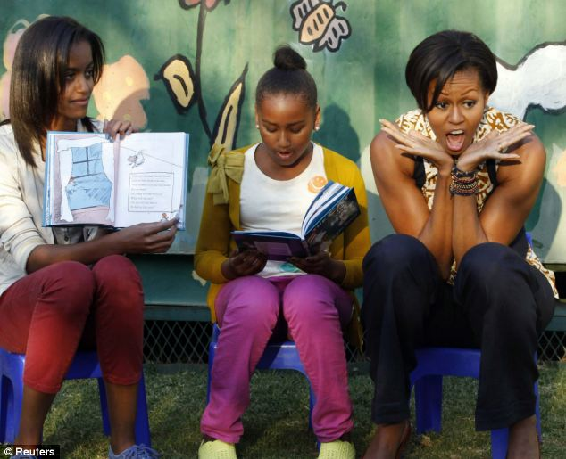 Reading time: Michelle Obama and daughters Sasha and Malia take turns reading to children from 'The Cat in the Hat' as they visit the Emthonjeni Community Center in Johannesburg
