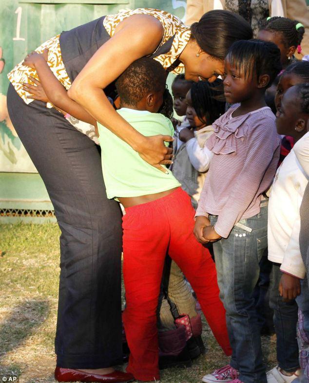 Embrace: Michelle Obama hugs children during her visit to the Emthonjeni Community Center