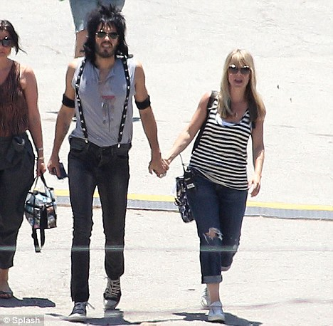 Tactile: Russell Brand can be seen holding the hand of a pretty blonde crew member on set in Miami today