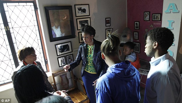Cutting it fine: The entourage is taken through a barber shop during a tour of the District Six museum
