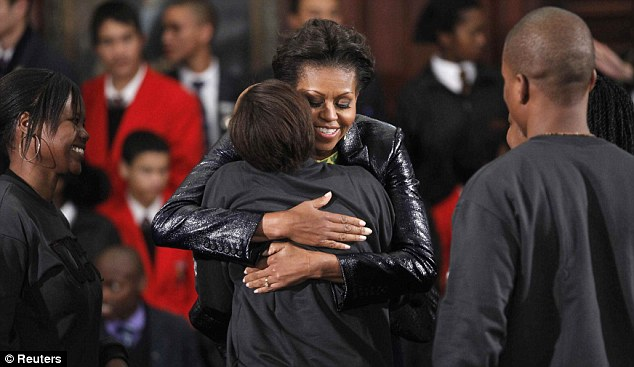 Embrace: Mrs Obama hugs a high school student after answering questions at the University of Cape Town