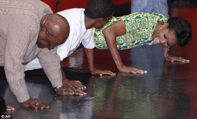 Work out: Michelle Obama does push ups with Archbishop Desmond Tutu as they participated in youth activities raising awareness for HIV prevention at Cape Town Stadium