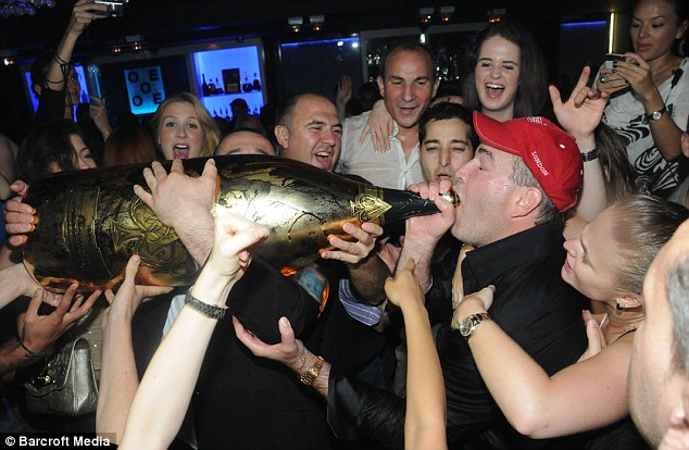 Best bubbly in town: Mr Johnson enjoys the taste of wealth as revelers help to lift the impressive bottle which broke the record for the previous most expensive champagne at £15,000