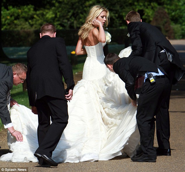 Where's a bridesmaid when you need one? Some of the wedding party help arrange Clancy's Giles Deacon dress