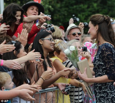 The Duchess of Cambridge greets the crowds as she takes part in a ceremony at the National War