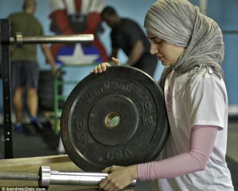 Weighty issue: Kulsoom Abdullah sets up her weights, she has persuaded the international weightlifting body to change its dress code for women