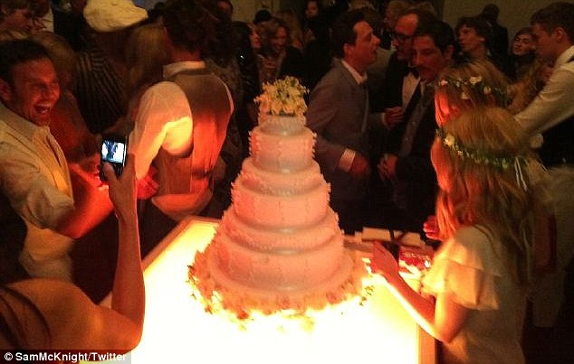 Yummy: Wedding guests, including the groom (just behind the cake to the right) gaze at the stunning cake