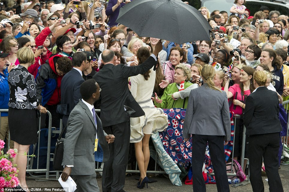 Wardrobe malfunction? Kate's skirt is caught by the wind as she greets fans in blustery and wet conditions
